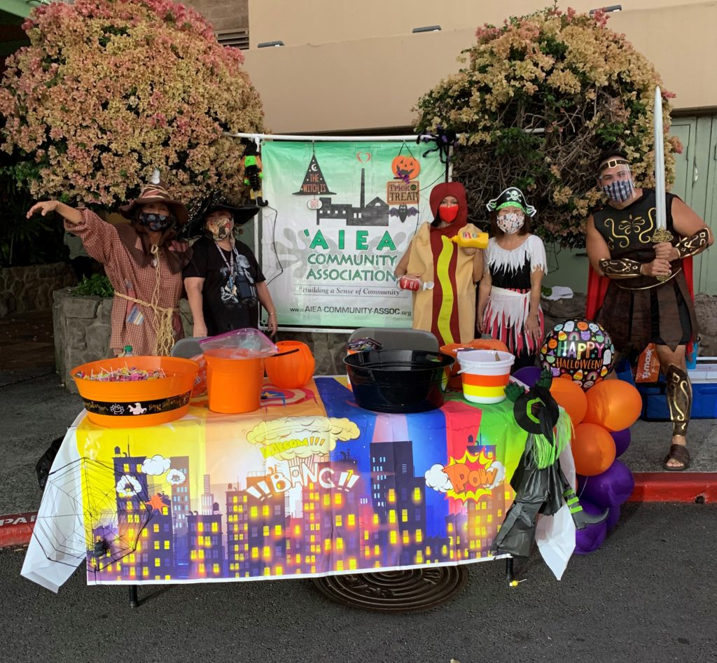Picture of five adults in Halloween costumes in front of a table decorated for Halloween.